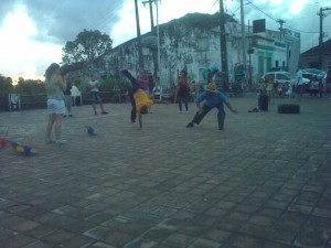 An amateur group casually dancing Capoeira in a small square.