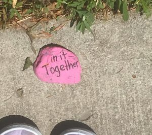 "Pink stone on sidewalk, painted to read ""in it together."""